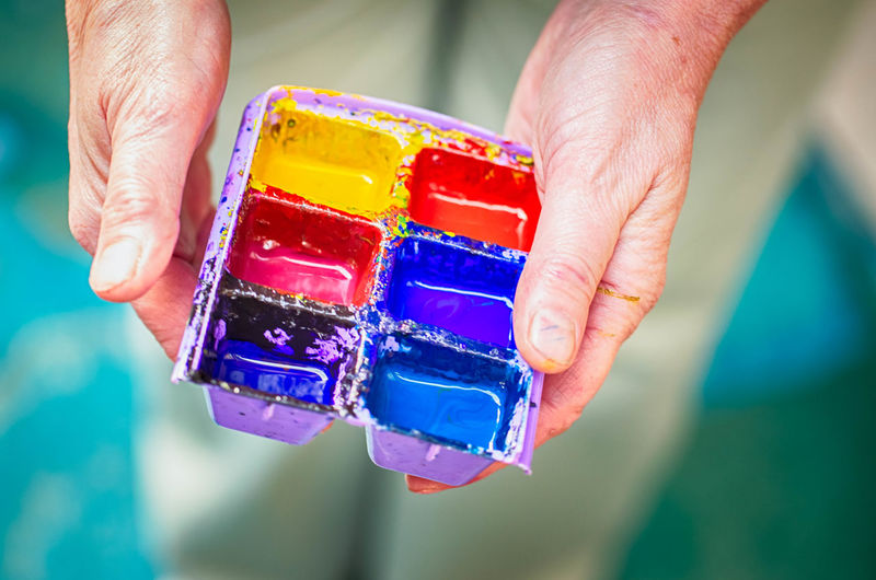 Midsection Of Person Holding Watercolor Paints In Palette