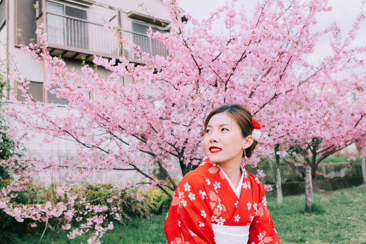 Woman standing against pink cherry blossom tree
