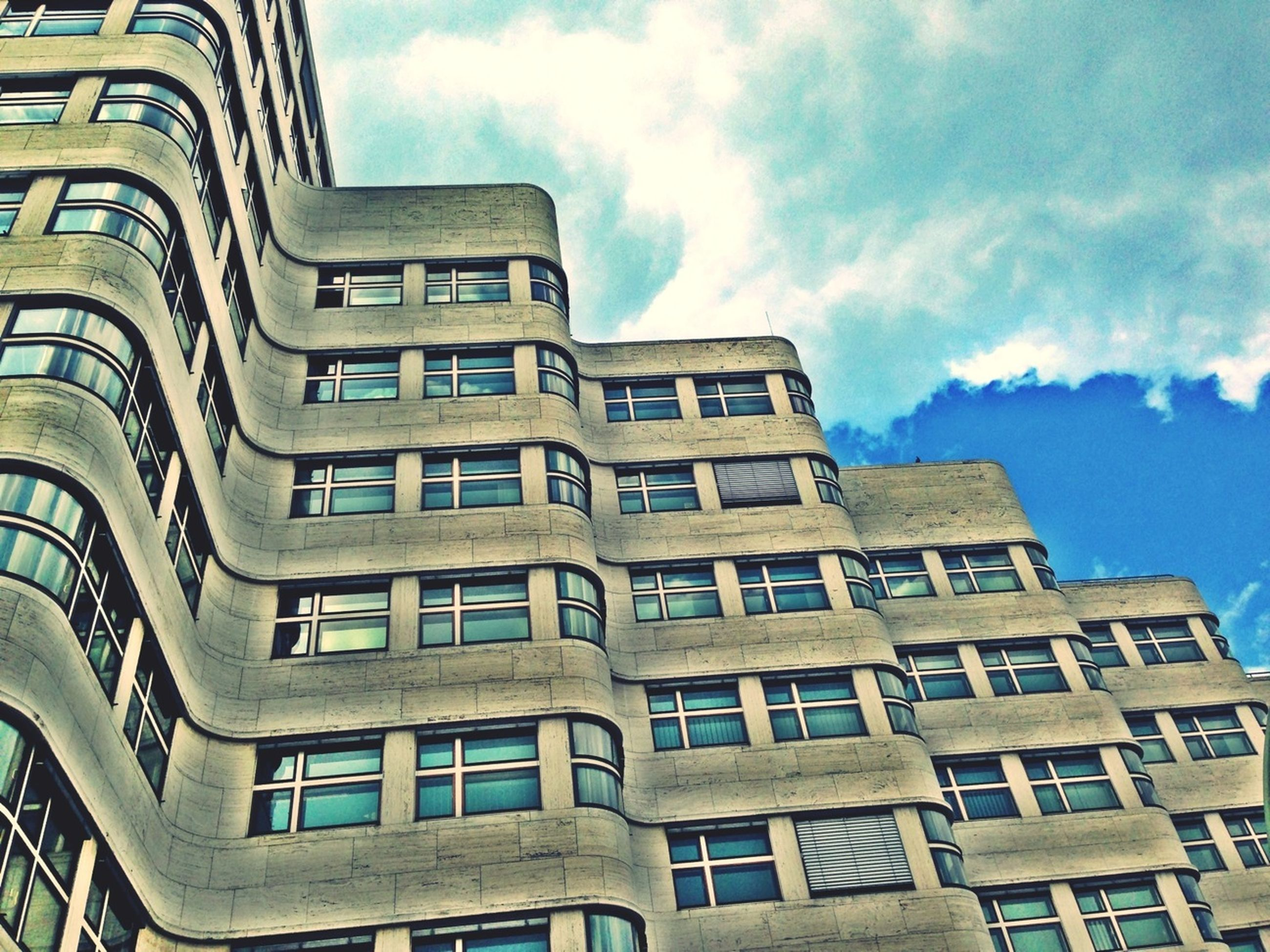 architecture, building exterior, built structure, low angle view, sky, window, building, residential building, residential structure, cloud - sky, city, balcony, cloud, day, apartment, no people, outdoors, glass - material, modern, cloudy