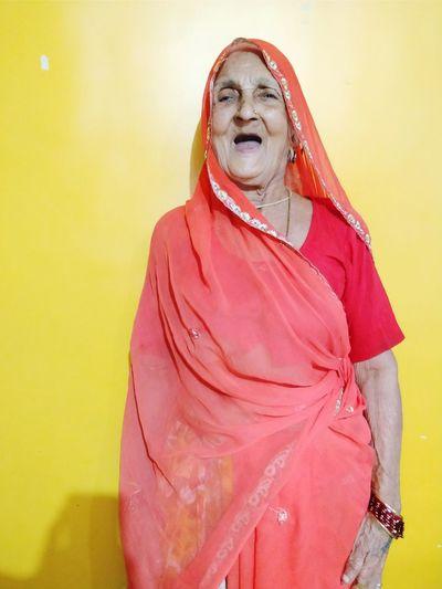 Senior Woman Wearing Sari Against Yellow Wall At Home