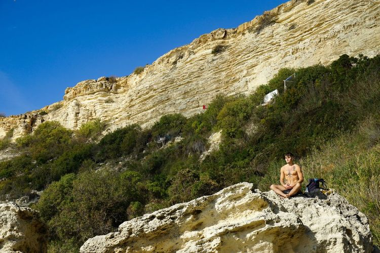 Low angle view of woman sitting on rock against sky