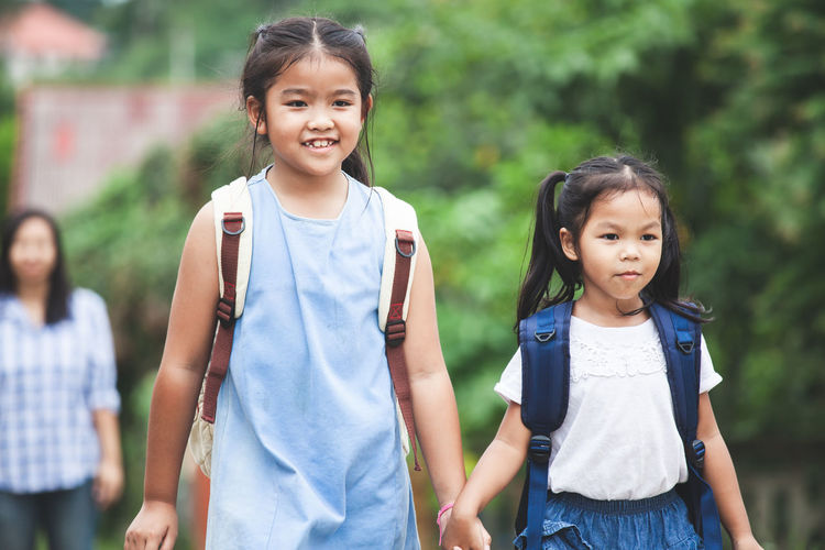 Back to school. Asian pupil kids with backpack holding hand and going to school together Asian  Family Happy Siblings Sister Student Walk Back To School Backpack Bag Child Cute Girl Holding Kid Knowledge Learn Pupil School Study Togetherness