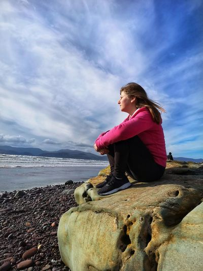 Girl Sitting On Rock At Beach Against Sky