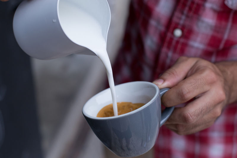 Midsection of man pouring milk in coffee cup