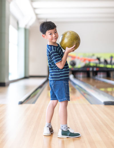 Asian family having fun at bowling club Ball Bowling Bowling Alley Bowling Balls Bowling Pins Boy Boys Child Childhood Flooring Happiness Indoors  Innocence Kid Lifestyles Men One Person Playing Portrait Pre-adolescent Child Real People Son Sport Standing Wood