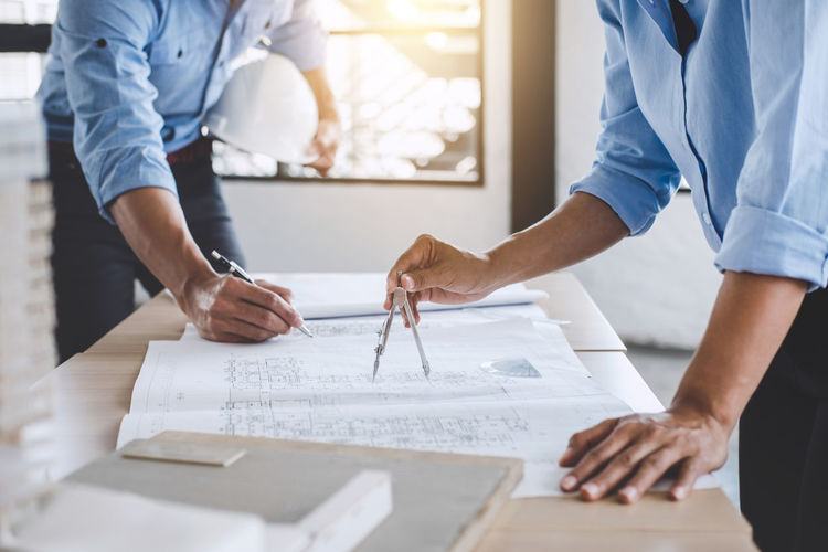 Midsection of architect preparing blueprints on table