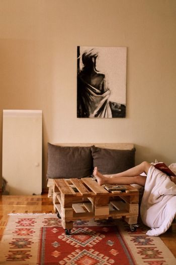 Low section of woman sitting on bed at home