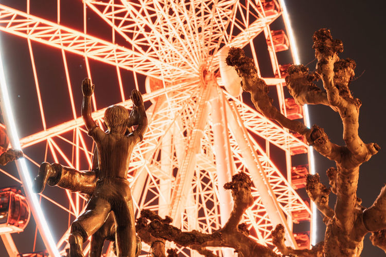 Low angle view of illuminated sculpture at night