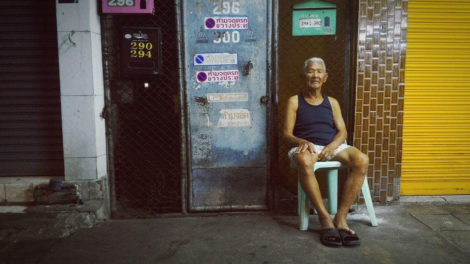 One Person Sitting Outdoors City Adults Only Full Length Adult People Portrait Streetphotography City Life Night Photography Thailand Artificial Light Old Man Sitting Urban Photography Urban Lifestyle Suburb Suburban Streets Plastic Chair Wall Side Road