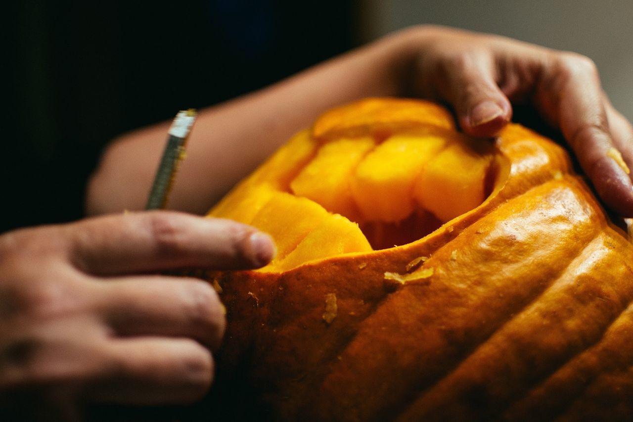 Cropped image of boy carving pumpkin for halloween