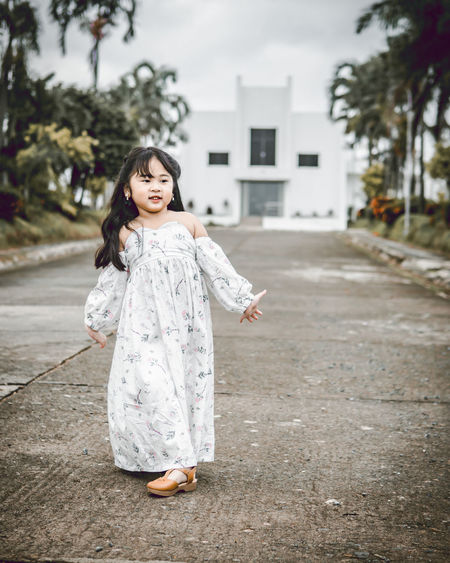 Cute smiling girl standing on footpath