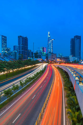 The busy traffic with blue hour in Saigon city, Vietnam. City Building Exterior Architecture Built Structure Long Exposure Motion Illuminated Light Trail Road Sky Speed Building City Life Transportation Street Blurred Motion Nature Office Building Exterior No People Cityscape Skyscraper Modern Outdoors Multiple Lane Highway