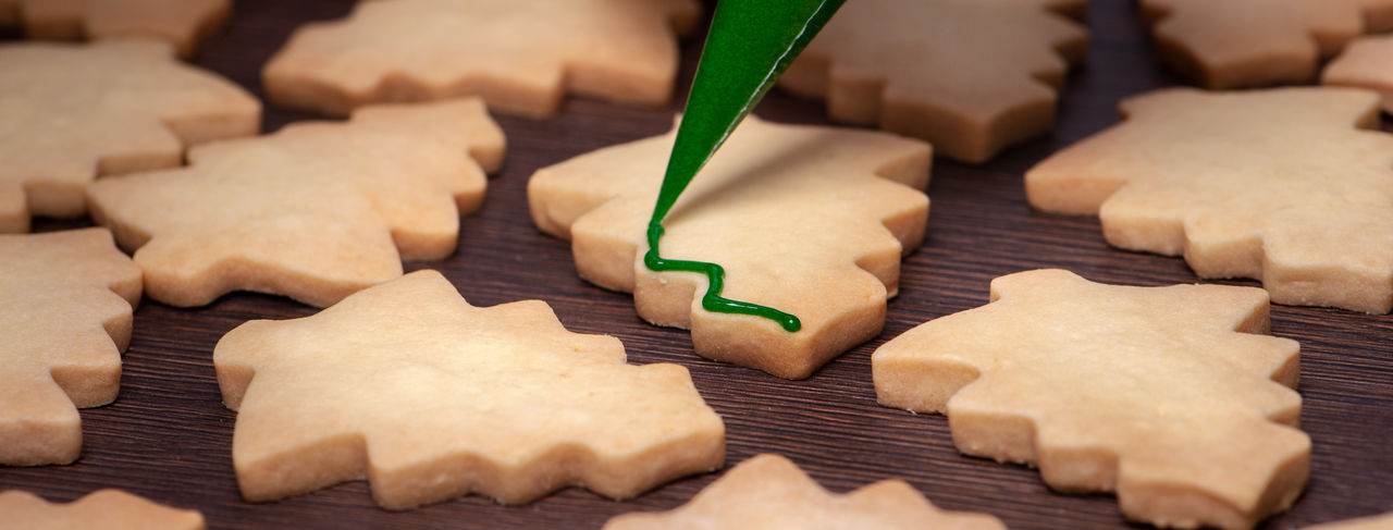 Close up of drawing christmas tree sugar cookie on wooden table background with icing.