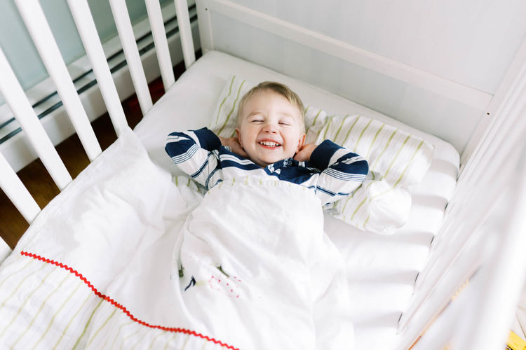 Portrait of smiling boy lying on bed