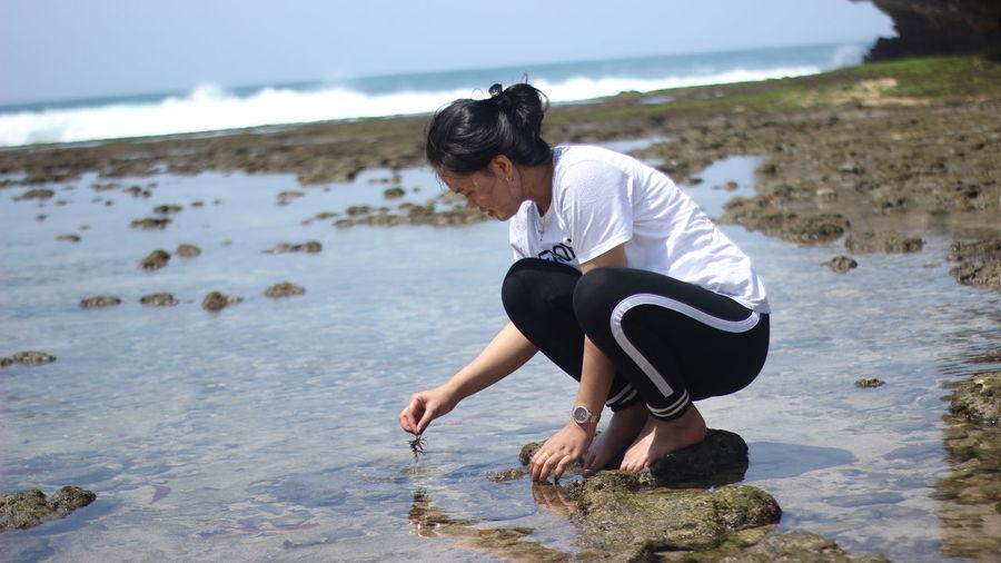 Full length of woman crouching at beach