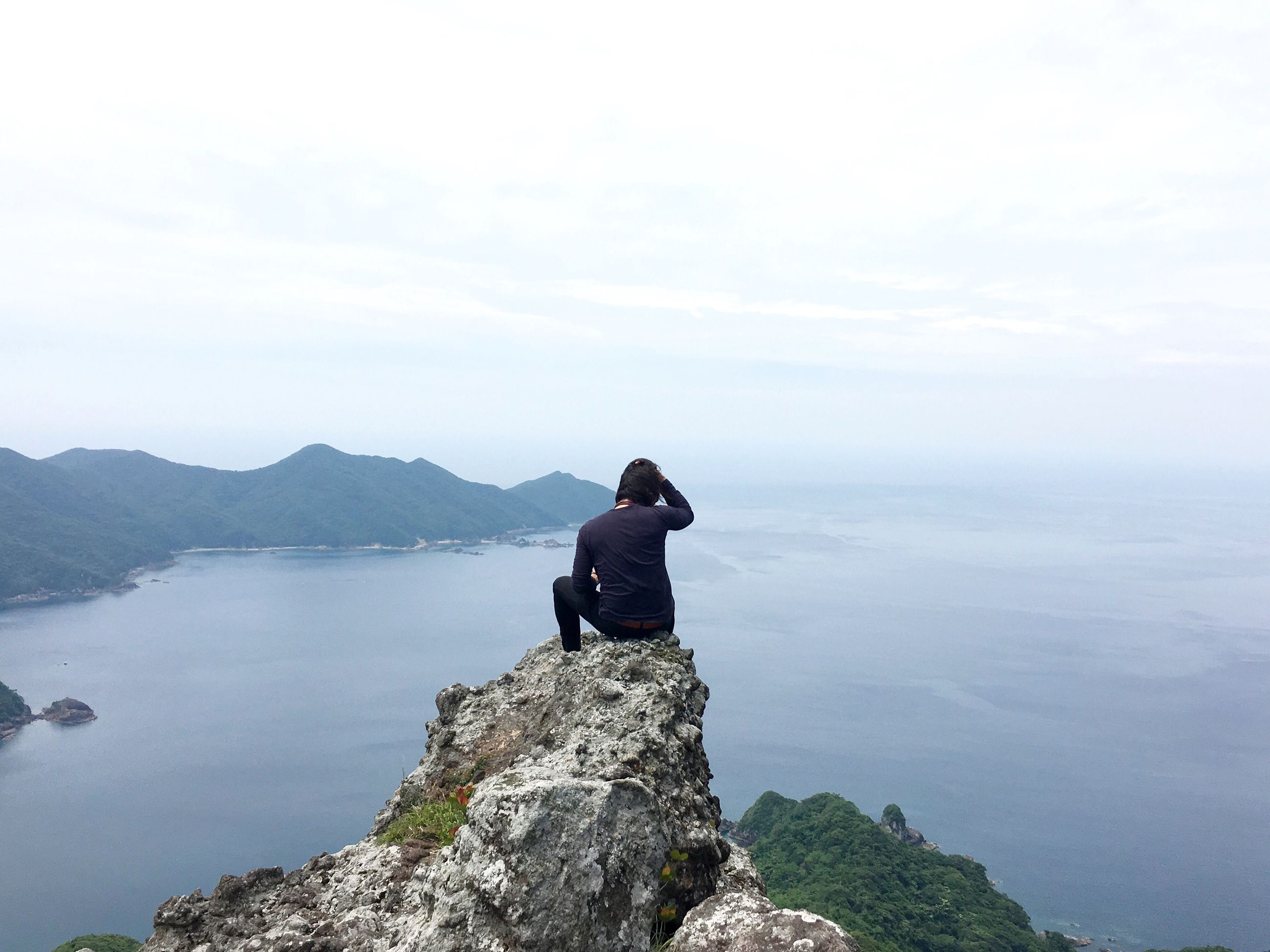 water, mountain, lifestyles, tranquil scene, standing, tranquility, leisure activity, scenics, beauty in nature, sky, rear view, sea, nature, getting away from it all, full length, looking at view, rock - object, three quarter length