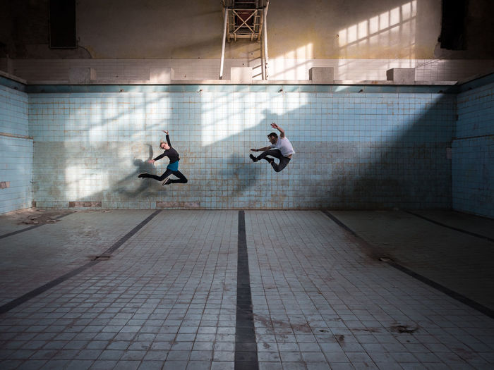Friends jumping in abandoned empty swimming pool