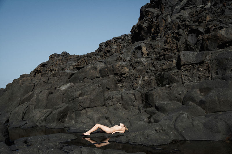 Naked woman lying on rocks by sea