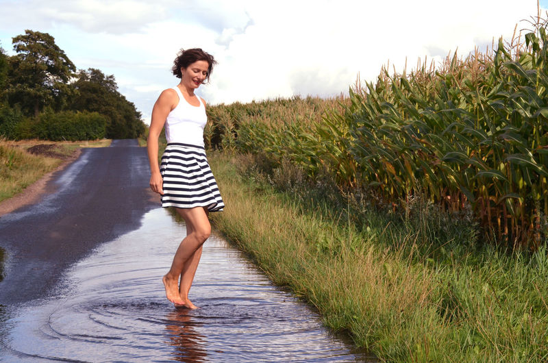 Natural Rain Adult Beautiful Woman Casual Clothing Day Full Length Grass Grey Sky Growth Hairstyle Land Leisure Activity Lifestyles Nature One Person Outdoors Plant Puddle Real People Standing Striped Water Women Young Adult