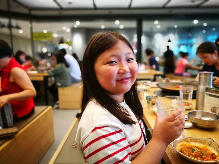 Portrait of smiling girl eating food in restaurant