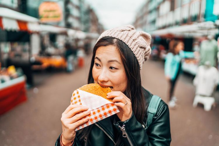 Portrait of woman eating food in city
