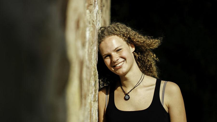 Portrait of happy beautiful woman leaning on wall