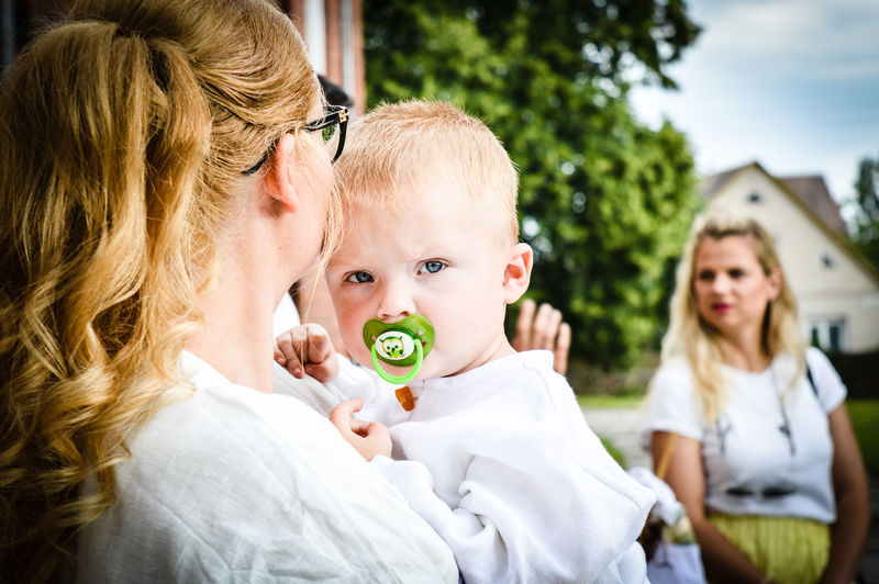 Close-Up Of Mother Holding Toddler Son While Standing Outdoors