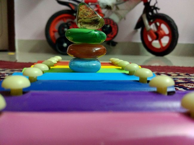 Stacking of stones above musical toys.. Multi Colored Close-up Abstractions In Colors Stonesteps