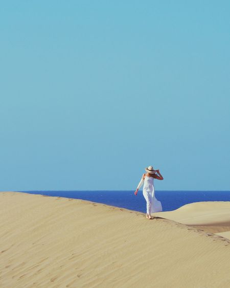 Woman walking at beach against clear sky