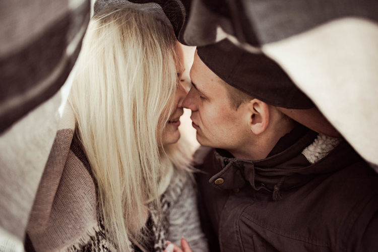 Close-up of couple kissing under blanket