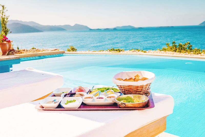 High angle view of food served on table at poolside against sea