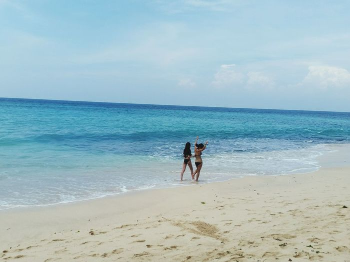 Rear view of women wearing bikini at beach against sky