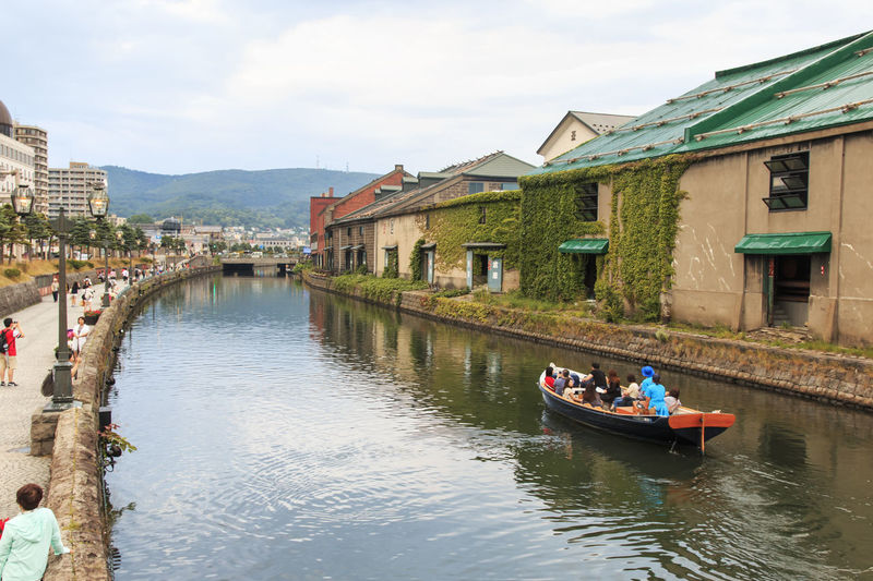 Otaru, Hokkaido - July 13,2015: Otaru, historic canal and warehousedistrict in Hokkaido, Japan, with many tourists walking by Architecture Boat Building Exterior Built Structure Canal City Life Cloud - Sky Day Furano Hokkaido In A Row Japan Japan Photography Mode Of Transport Nautical Vessel Otaru Passenger Craft River Sky Spring Tourism Transportation Travel Destinations Water Waterfront