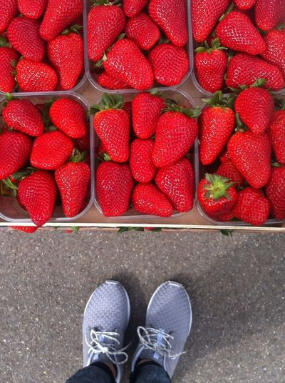Low section of person standing by strawberries for sale in market