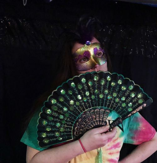 Close-up of woman with mask and folding fan