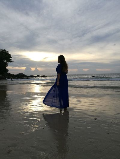 Woman Standing On Shore At Beach Against Sky During Sunset
