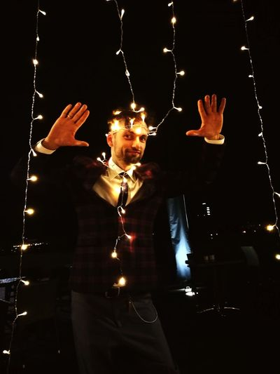 Portrait of man wearing illuminated lights while standing in darkroom