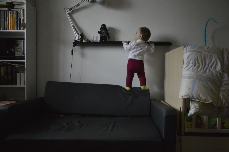 Rear view of boy standing on sofa at home