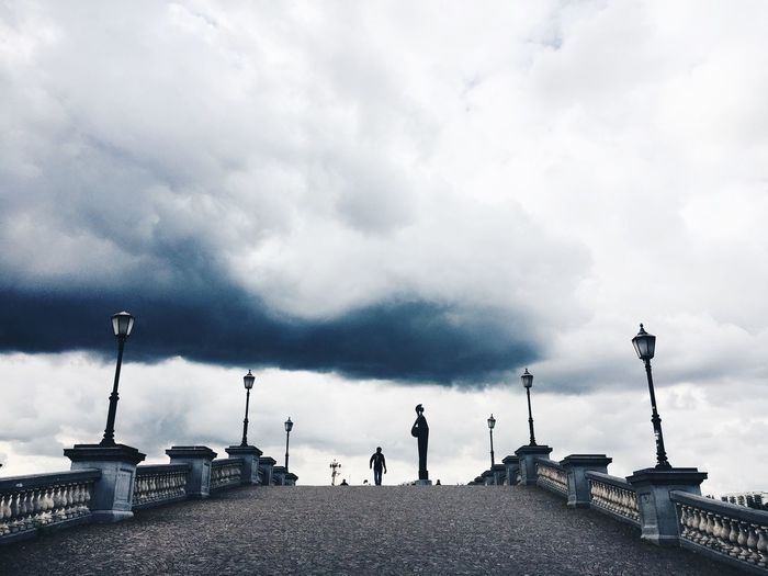 Rear view of a woman standing against cloudy sky