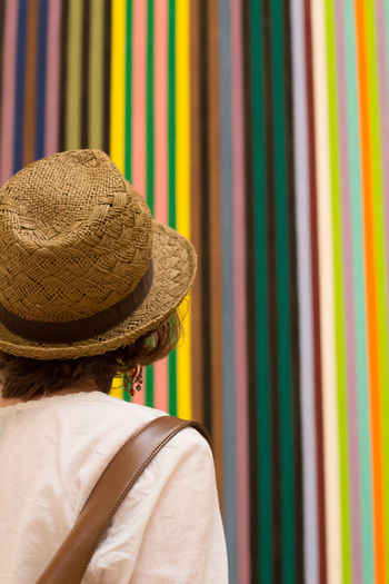 Rear view of woman looking at striped wall