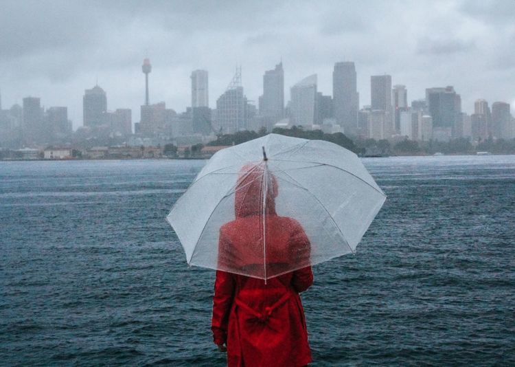 Person With Umbrella Standing In Rain During Rainy Season