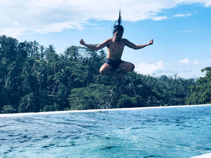 Shirtless man jumping in infinity pool against forest