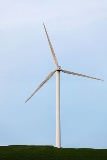 Low angle view of windmill on field against clear sky