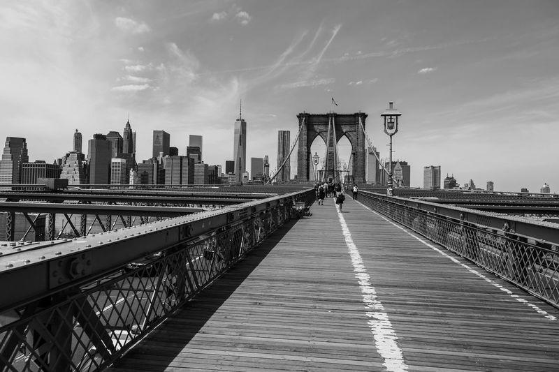 Brooklyn bridge by modern buildings against sky