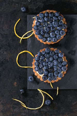 Two Lemon tartlets with fresh blueberries, served on black stone slate with lemon and lemon zest over black background. Top view. With space for text Berries Black Background Desserts Lemon Tarte Shortbread Berry Tartlet Blackberry Blueberry Blueberry Tart Directly Above Food Lemon Zest Pastry Shortbread Tartlet Slate Sweet Food Tart - Dessert Tartlet Top View Of Food