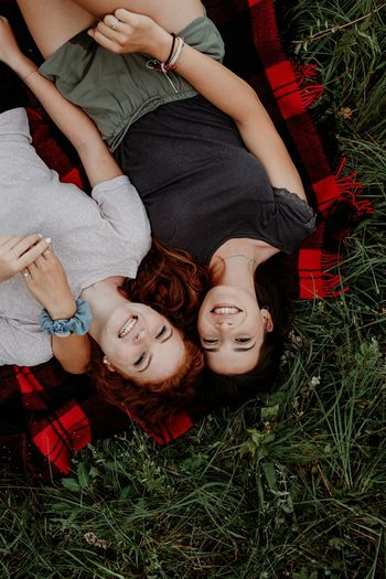 High angle portrait of friends relaxing on field
