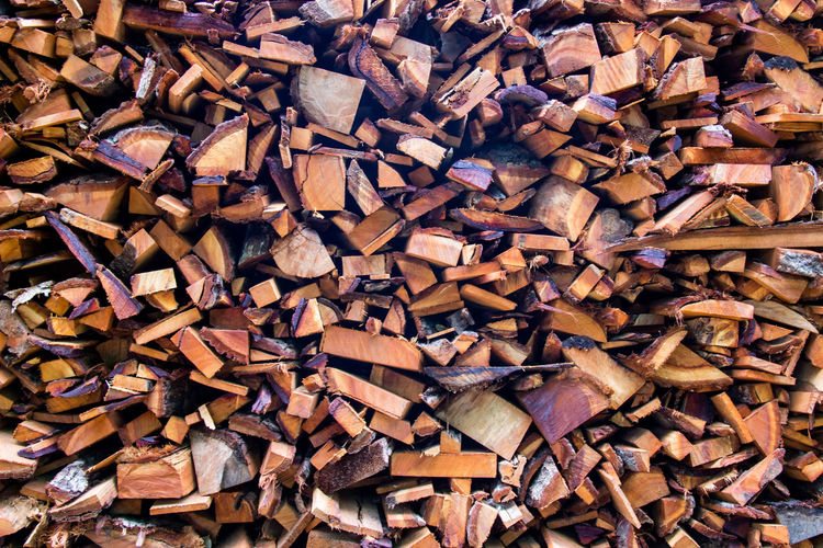 Firewood wooden logs big chopped trunks stacked pile dry for the used fireplace in winter.