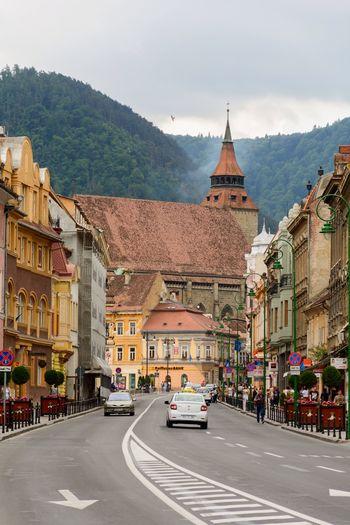 Street Amidst Buildings Against Cloudy Sky