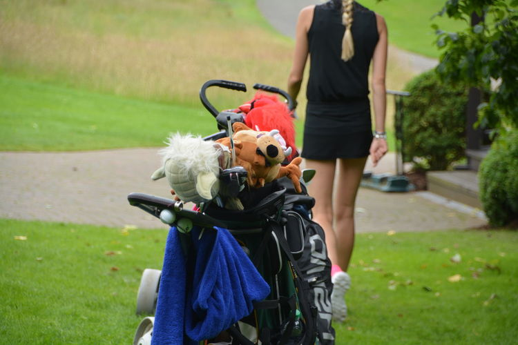 Stuffed toys in golf bag with woman walking in background