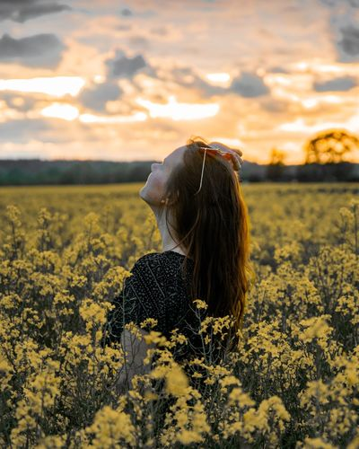 Woman standing amidst yellow flowers on field during sunset